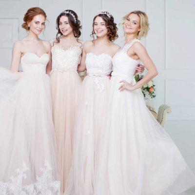 Bride in wedding salon. Four beautiful girl are in each other's arms. Close-up lace skirts