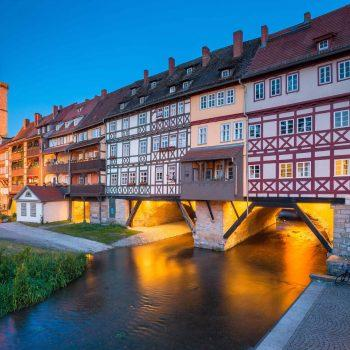 Classic panoramic view of the historic city center of Erfurt with famous Krämerbrücke bridge illuminated at beautiful twilight during blue hour, Thüringen, Germany